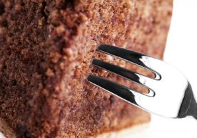macro closeup of a fork in a chocolate cake on white background
