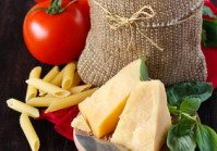 Ingredients for preparing pasta. Cheese, tomatoes, basil and pasta in a bag on a dark wooden background.