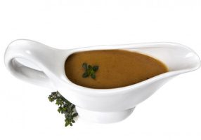 Thyme gravy in white gravy boat, isolated.  Delicious!